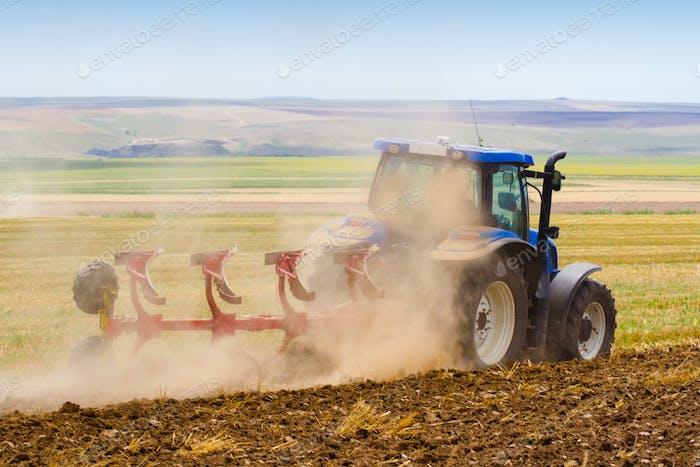 Traktor pflügt ein Feld mit Spur von Staub