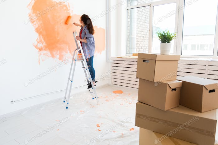 Happy young woman painting interior wall with paint roller in new house. A woman with roller