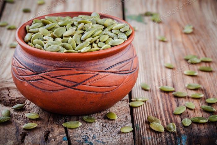 organic pumpkin seeds in a clay bowl