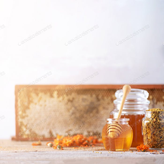 Herbal honey in jar with dipper, honeycomb, bee pollen granules, calendula flowers on grey