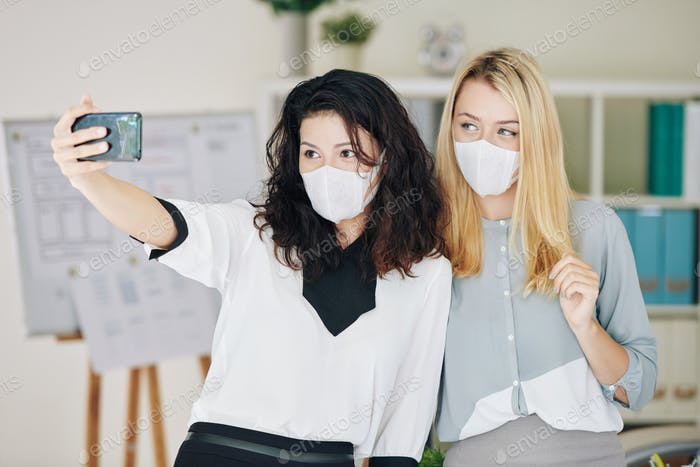Woman in medical mask photographing with colleague