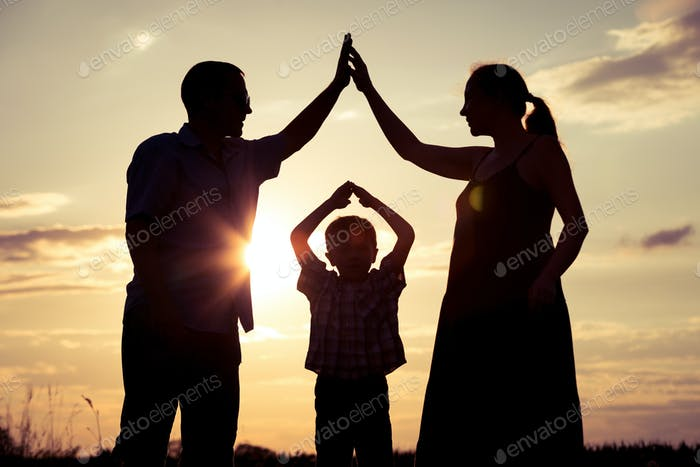 Happy family standing on the field at the sunset time.
