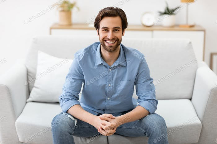 Happy Man Sitting On Couch Smiling To Camera At Home
