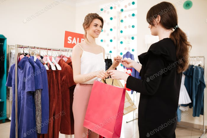 Nice girl in white top making a purchases in clothes store with sale clothes rack on background