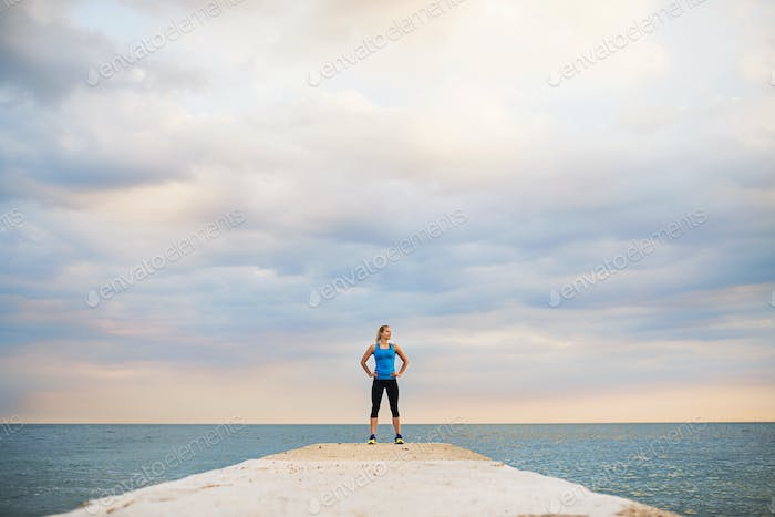 A young sporty woman standing on a pier by the ocean outside.