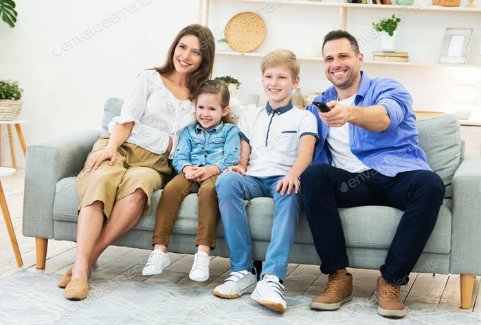 Family Of Four Watching TV Sitting On Sofa Indoors