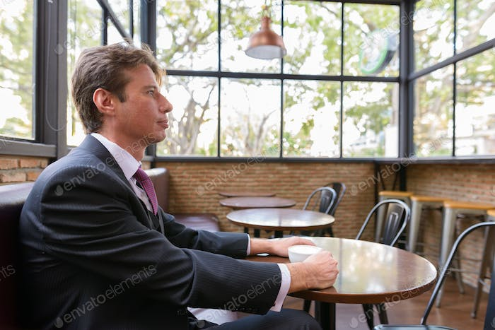 Profile view of businessman drinking coffee and thinking at the