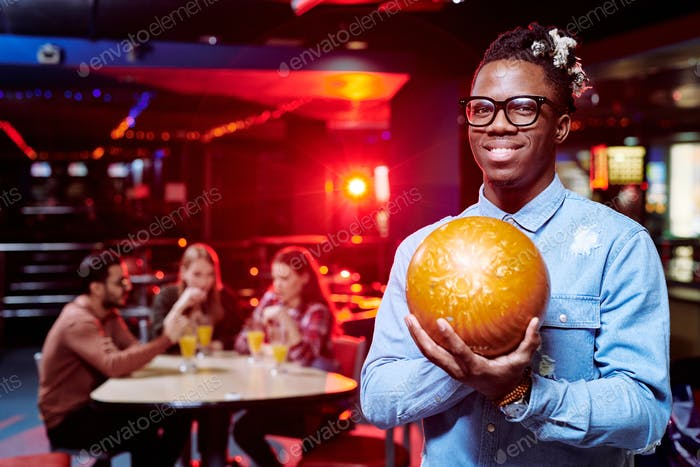 Happy young African man with bowling ball standing in front of camera
