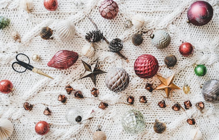 Christmas decoration toys and balls over knitted woolen background