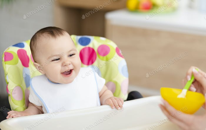 Adorable baby enjoying porridge, sitting in high chair at kitchen