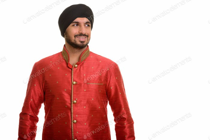 Young happy Indian Sikh thinking while wearing traditional cloth