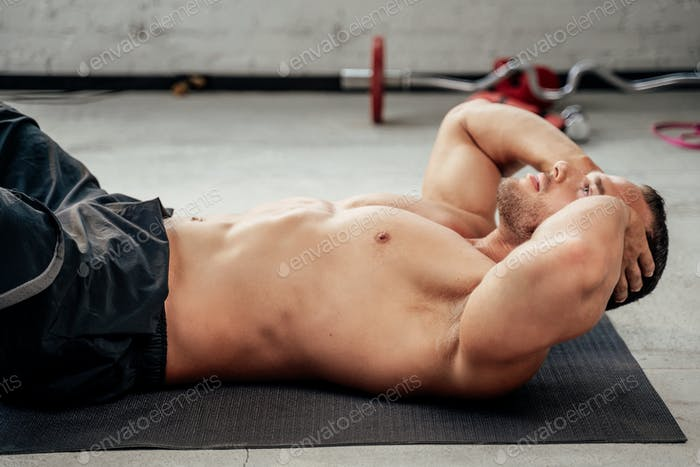 Handsome bodybuilder training his abs on floor in gym