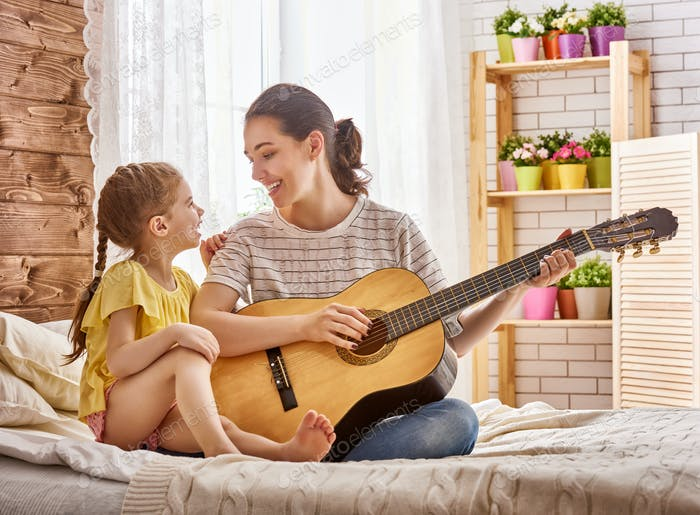 woman playing guitar for child girl