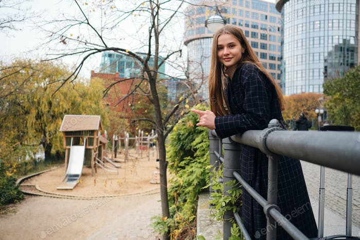 Pretty casual girl in coat happily looking in camera resting alone in park