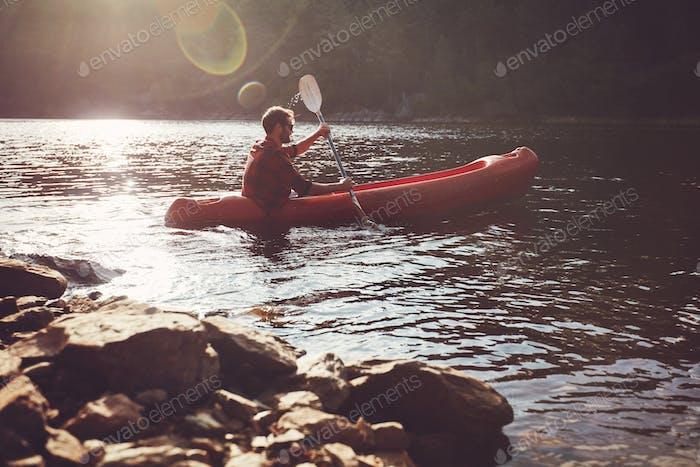 Junger Mann Kajakfahren in einem See