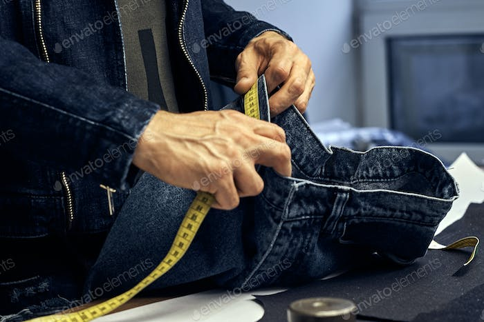 Cropped image of tailor makes measurements of jeans with a meter at sewing workshop.