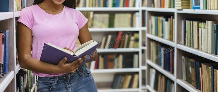Afro girl holding open book, leaning on bookshelf