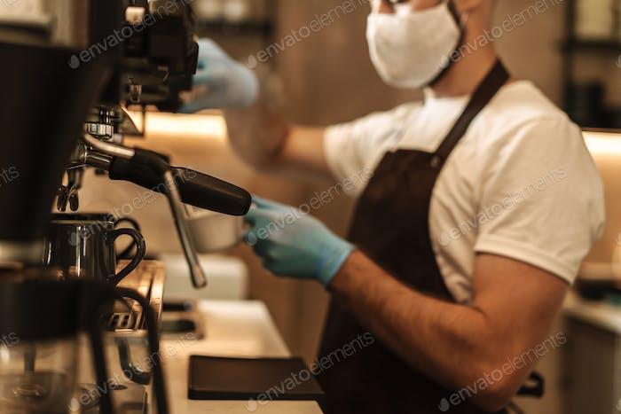 barista equipado con una máscara protectora para el virus