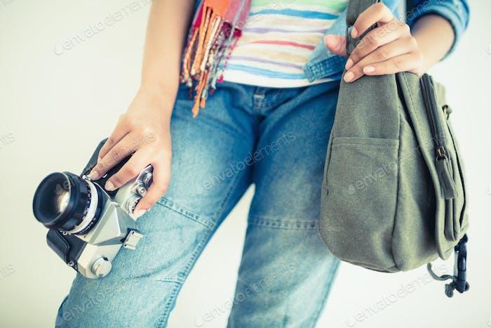 Frau in Denim hält Kamera und Schultertasche auf weißem Hintergrund