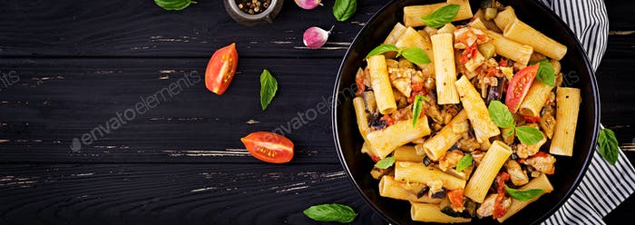 Rigatoni pasta with chicken meat, eggplant in tomato sauce in bowl. Italian cuisine