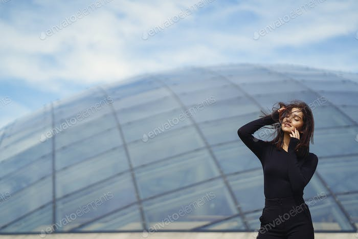 brunetter girl next to a modern building