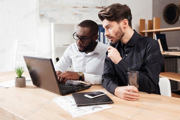 Молодые многонациональные бизнесмены, заботливо работающие с ноутбуком вместе в офисе