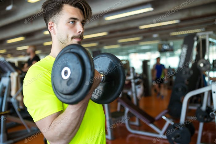 Handsome young man doing muscular exercise in gym.