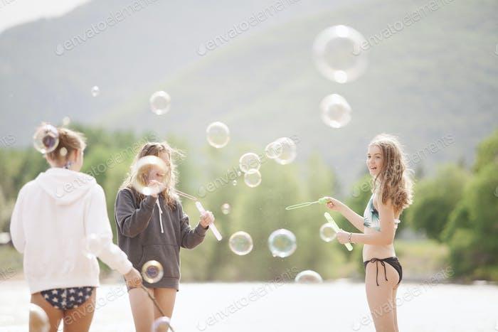 Девочки-подростки стоят у озера, в окружении мыльных пузырей.