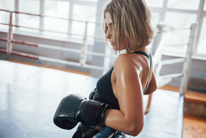 Nasse Haut und Haare. Sportlerin im Boxring. In schwarz gefärbten Kleidern