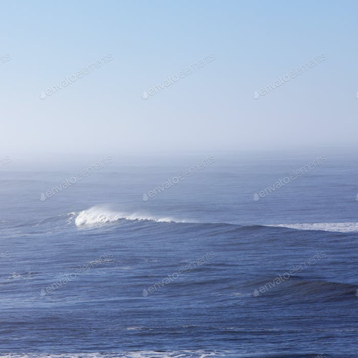 A view over the ocean, and a wave with a developing white crest.