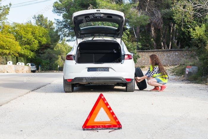 A broken car, a sign of an accident and a woman understands what's the matter