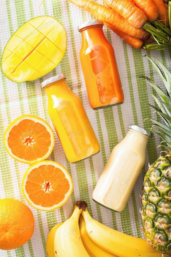 fruit and vegetable smoothies in glass jars, orange mango banana