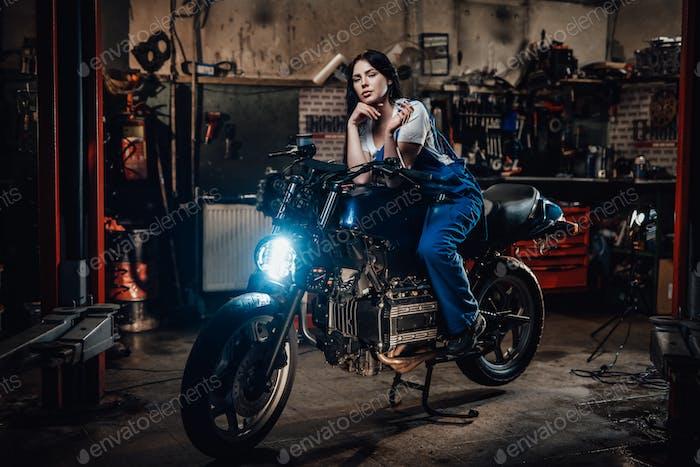 Красивая брюнетка байкер или механик расслабляющий курить сигарету в гараже или мастерской