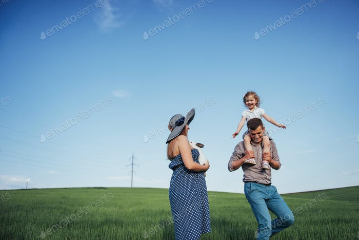 Happy family of three people hugging in the streets