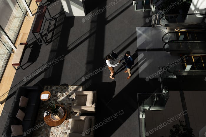 High angle view of young multi-ethnic business executives shaking hand standing in modern office