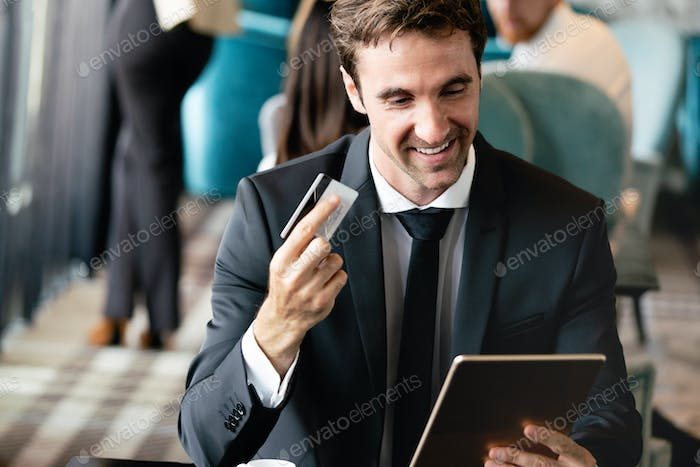 Portrait of young man holding tablet pc and credit card