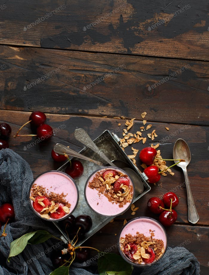Cherry smoothie in a glass topped with fresh cherries and granola
