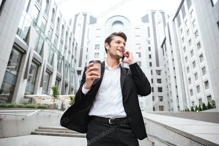 Happy young businessman talking on mobile phone and drinking coffee