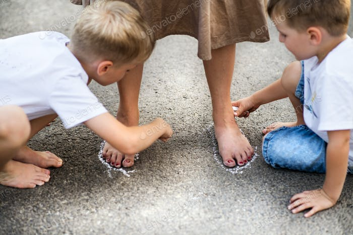 Two small sons playing with mother on a road in park on a summer day.