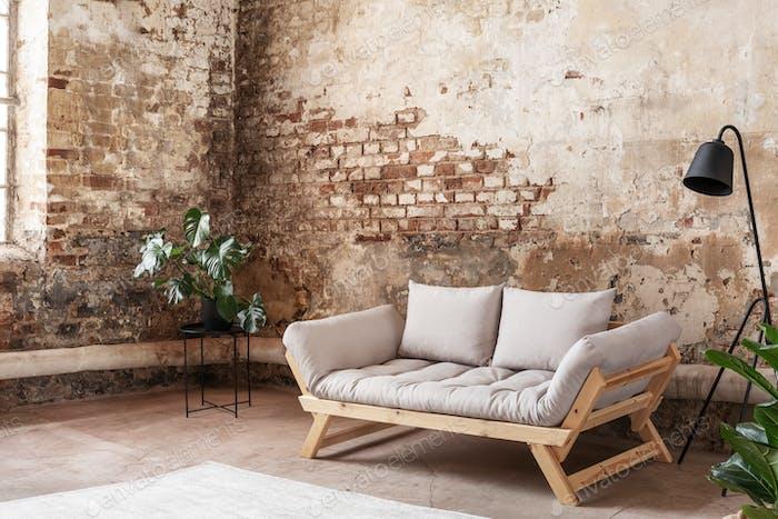 Grey sofa between plant and black lamp in wabi sabi loft interio