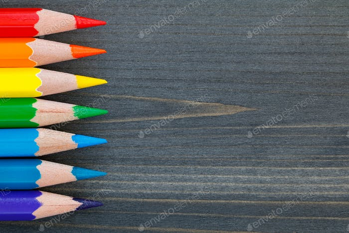 Top view on colored pencils on a blackboard. Macro shot.