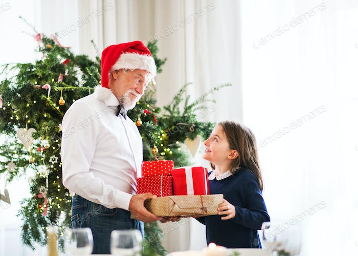 A senior man with a Santa hat giving presents to a small girl at Christmas time.