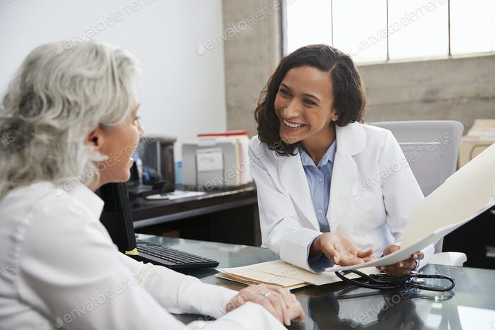 Smiling female doctor in consultation with senior patient