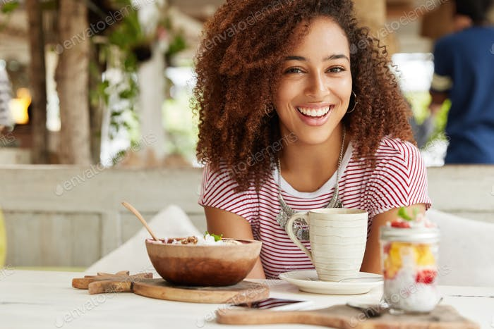 Good looking curly female with happy appearance and curly hair drinks coffee with dessert on terrace