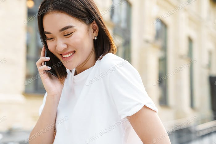 Happy young asian woman talking by mobile phone