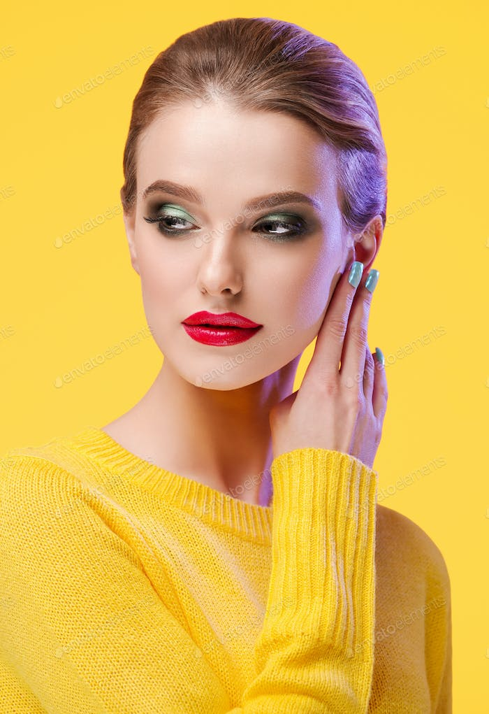 Colorful makeup woman in yellow clothes on color summer background
