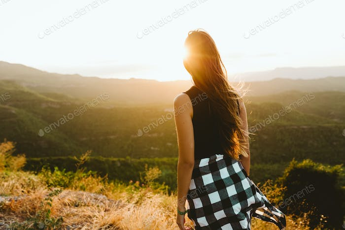 Beautiful young woman enjoying nature at mountain peak.