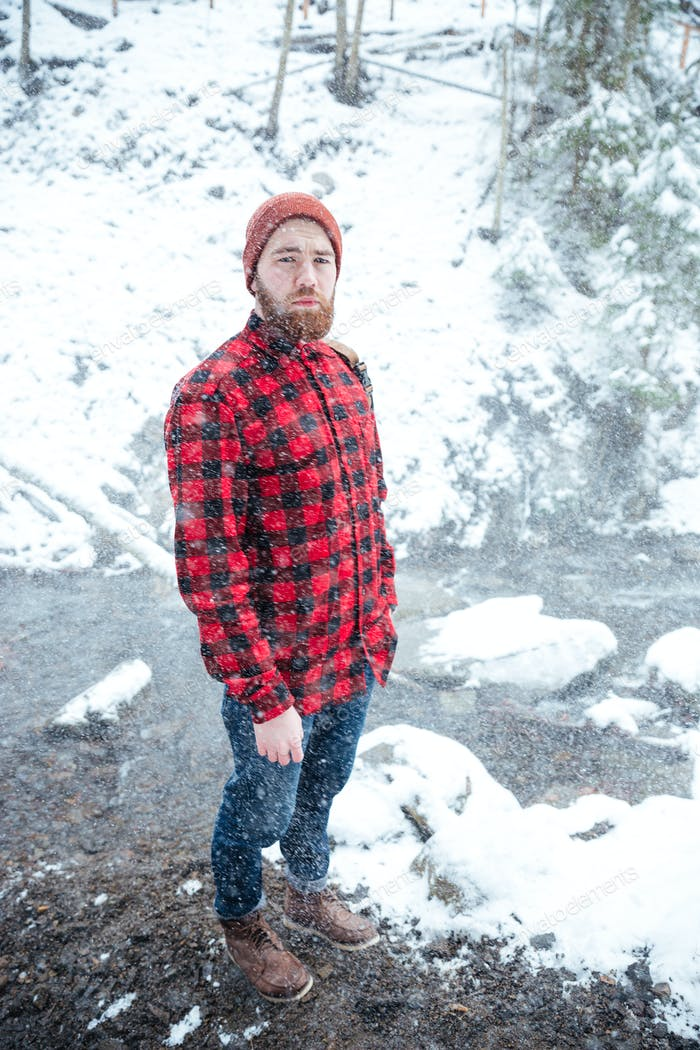 Man with beard standing at winter forest in snowy weather