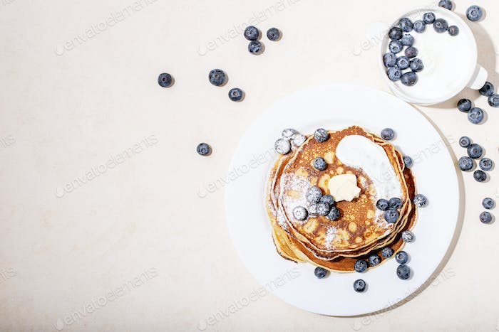 A stack of plain pancakes served with honey and blueberry