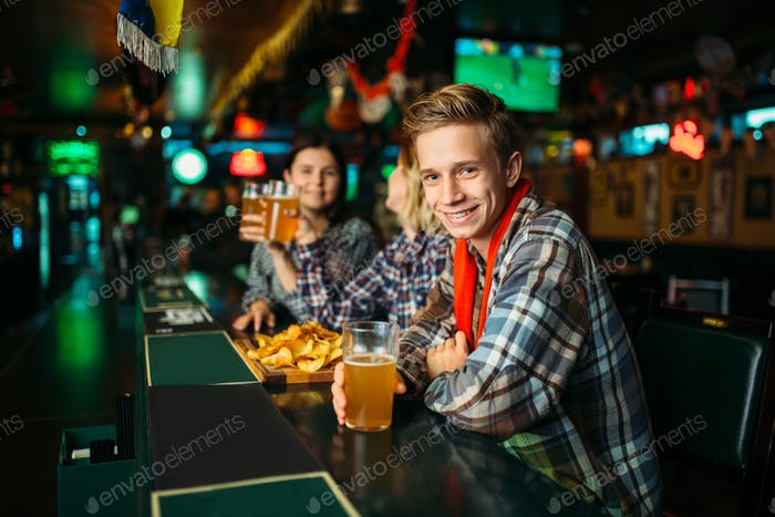 Fans mit Gläsern Bier an der Theke in der Sportbar